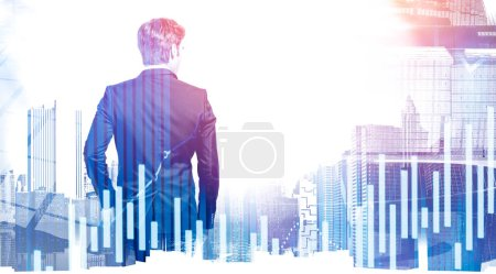 Photo for Rear view of young broker looking at modern city with double exposure of blurry digital charts. Concept of stock market and leadership. Toned image - Royalty Free Image