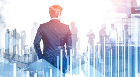 Photo for Rear view of business leader and silhouettes of his colleagues in modern city with double exposure of HUD interface and graphs. Concept of leadership. Toned image - Royalty Free Image