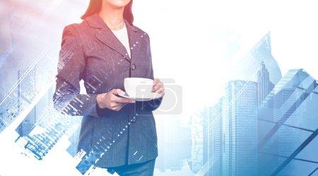 Foto de Joven empresaria irreconocible sosteniendo taza y platillo en la borrosa ciudad moderna. Concepto de liderazgo y coffee break. Imagen tonificada doble exposición - Imagen libre de derechos