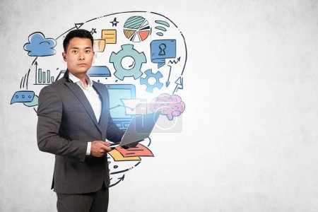 Photo for Serious young Asian businessman holding laptop near concrete wall with colorful business idea sketch drawn on it. Concept of planning. Mock up - Royalty Free Image