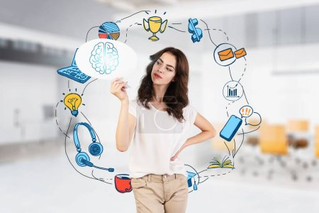 Photo for Beautiful young businesswoman holding speech bubble with brain drawn on it in blurry office with double exposure of colorful business plan sketch. Concept of business strategy. Toned image - Royalty Free Image
