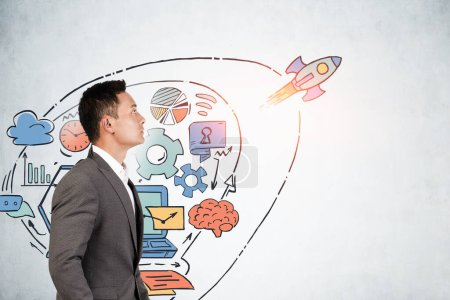 Photo for Side view of creative young Asian businessman looking at colorful startup sketch drawn on concrete wall. Concept of new project launch. Mock up - Royalty Free Image