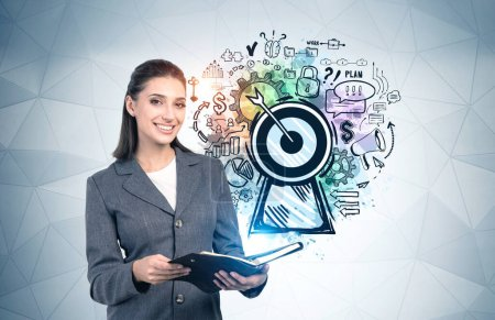 Photo for Portrait of cheerful young businesswoman with planner standing near gray wall with colorful big goal sketch drawn on it. Concept of success, career and planning - Royalty Free Image