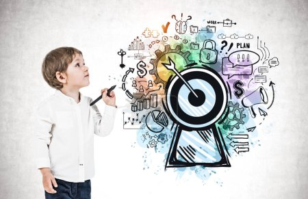 Photo for Adorable little boy with marker standing near concrete wall with colorful big goal sketch drawn on it. Concept of education, skills and career - Royalty Free Image