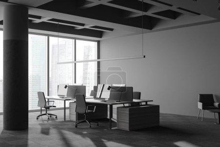 Photo pour Coin du loft panoramique bureau à aire ouverte avec murs gris, sol moquette, colonnes et tables d'ordinateur grises et en bois. Fenêtre avec paysage urbain flou. Rendu 3d - image libre de droit