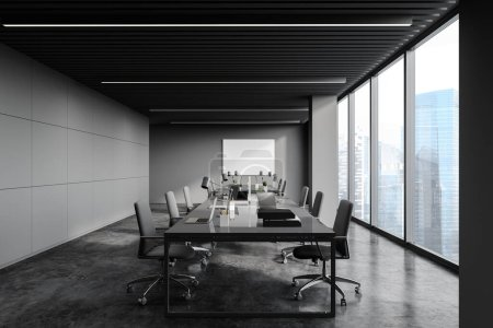 Photo for Front view of loft panoramic open space office with dark gray walls, concrete floor, long computer tables, horizontal mock up poster and window with blurry cityscape. 3d rendering - Royalty Free Image