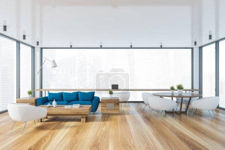 Photo pour Intérieur du salon panoramique avec canapé bleu, table basse, table à manger ronde avec fauteuils blancs et espace bureau près de la fenêtre avec paysage urbain flou. Rendu 3d - image libre de droit