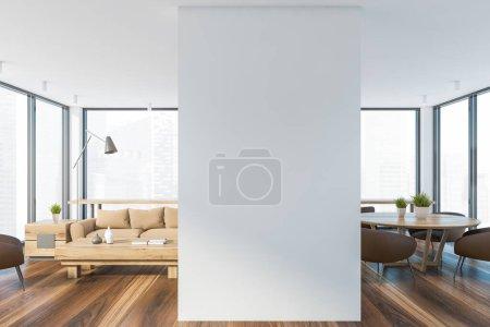 Photo pour Intérieur du salon moderne avec des murs blancs, confortable canapé beige debout près de la table basse et salle à manger avec table ronde et fauteuils marron à côté. Paysage urbain flou. Rendu 3d - image libre de droit