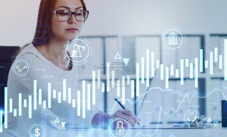Photo for Serious young European businesswoman in glasses taking notes in blurry office with double exposure of digital graphic interface. Concept of stock market and analytics. Toned image - Royalty Free Image