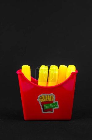 Photo pour Fast-food. frites en plastique français sur un fond noir. copier l'espace. vertical - image libre de droit