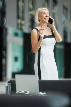 Photo for Busy mature businesswoman talking on mobile phone - Royalty Free Image