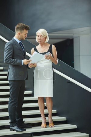 Photo for Mature businesswoman in elegant dress discussing business contract together with partner while standing on stairs at office - Royalty Free Image