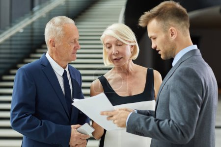Photo for Young businessman holding document showing to colleagues and discussing in team at modern office - Royalty Free Image
