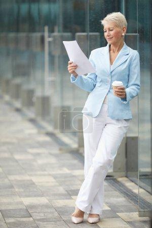 Photo pour Femme d'affaires mature en beau costume lire rapport d'entreprise et boire du café avant de rencontrer debout à l'extérieur - image libre de droit