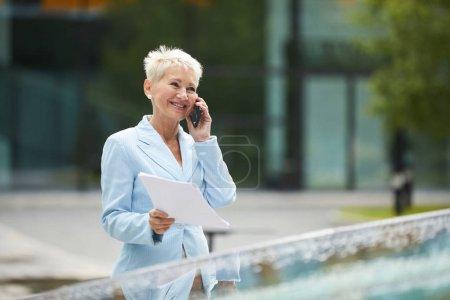 Foto de Madura sonriente mujer de negocios con el pelo corto rubio hablando a través de teléfono inteligente caminando por la calle en la ciudad - Imagen libre de derechos
