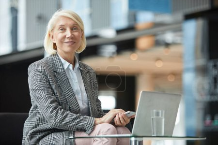 Photo for Portrait of mature blond businesswoman sitting at the table with laptop holding mobile phone and smiling at camera at office - Royalty Free Image