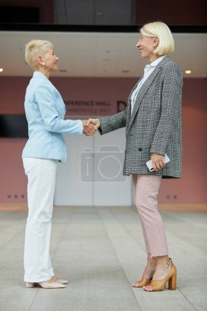 Photo for Smiling mature businesswomen standing and shaking hands during meeting - Royalty Free Image