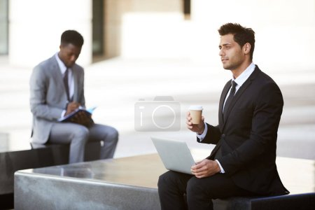 Photo for Pensive businessman sitting with laptop on knees working outdoors in the city with man in the background - Royalty Free Image