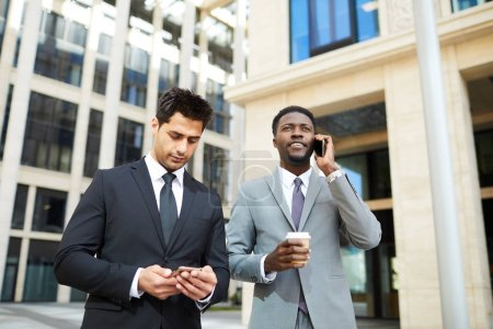 Photo for Two young businessmen in suits using mobile phones talking while walking along the street in the city - Royalty Free Image