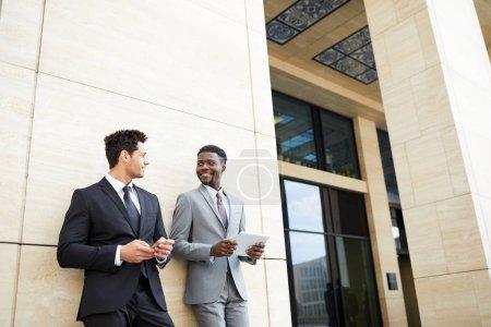 Foto de Dos jóvenes colegas de negocios que usan ropa formal apoyada en la pared del edificio de oficinas y usan aparatos modernos al aire libre - Imagen libre de derechos