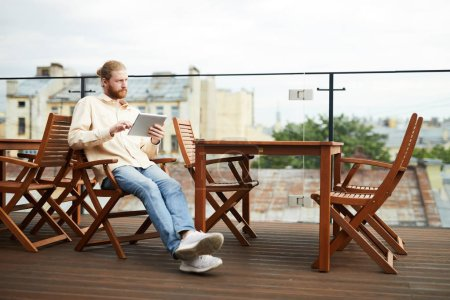 Photo for Young bearded man sitting on chair and using digital tablet during leisure time in outdoor cafe - Royalty Free Image