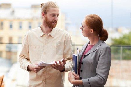 Foto de Dos jóvenes socios comerciales que tienen documentos y carpetas y discuten juntos los planes de negocios mientras están al aire libre - Imagen libre de derechos
