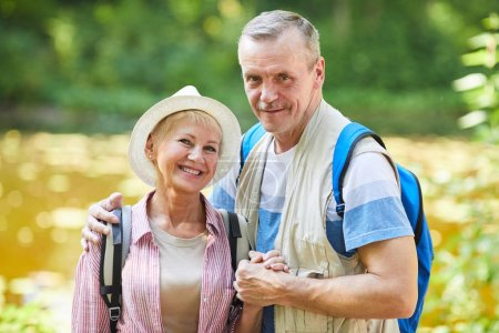 Photo pour Portrait de randonneurs seniors avec des sacs à dos souriant à la caméra tout en étant debout dans la nature à l'extérieur - image libre de droit