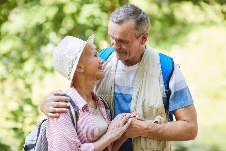 Photo pour Senior couple heureux randonnée dans la forêt debout tenant la main et se regardant avec tendresse - image libre de droit