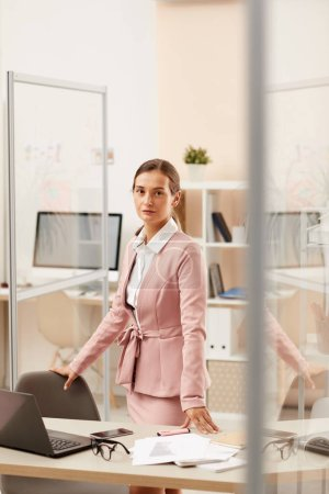Photo for Portrait of young office worker in pink formal suit looking at camera with serious expression at office - Royalty Free Image