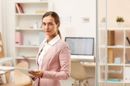 Photo pour Portrait de jeune femme d'affaires en costume rose élégant travaillant dans un bureau moderne - image libre de droit