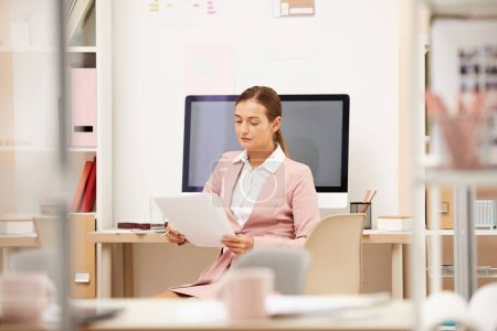 Photo for Young businesswoman sitting workplace and concentrating on online work - Royalty Free Image