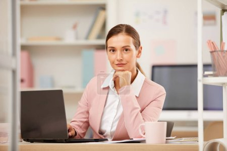 Photo for Portrait of young office manager sitting at the table in front of laptop and working with documents - Royalty Free Image