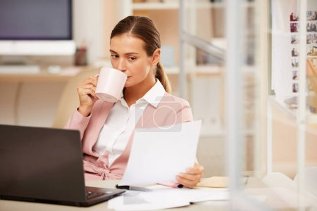 Photo for Portrait of young businesswoman sitting at the table with laptop holding cup of coffee at office - Royalty Free Image