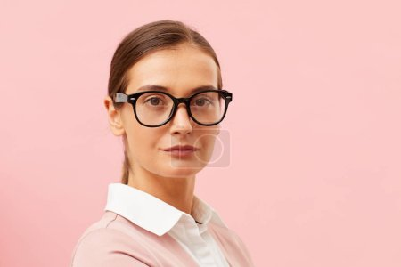 Photo for Portrait of young beautiful woman wearing eyeglasses and looking at camera on pink background - Royalty Free Image