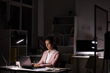 Photo for Young serious woman sitting and typing on laptop under the lamp standing on table in dark office - Royalty Free Image