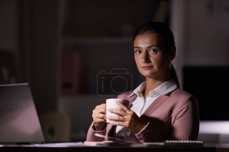 Photo for Portrait of young woman looking at camera while sitting at the table and drinking coffee after work in dark office - Royalty Free Image
