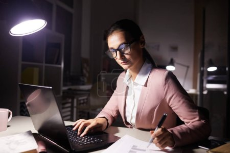 Photo for Young businesswoman in eyeglasses concentrating on online work on laptop computer sitting at the table and working till night - Royalty Free Image