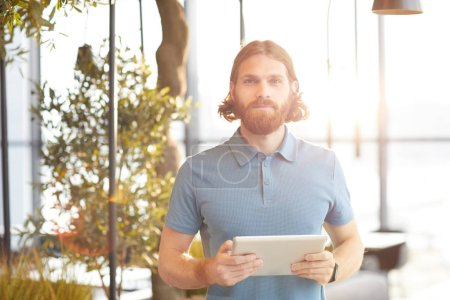 Photo for Portrait of red haired bearded young man holding digital tablet and looking at camera while standing in cafe - Royalty Free Image