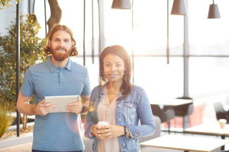 Photo pour Portrait de jeune couple occasionnel avec tablette pc et boisson au café debout dans le café - image libre de droit