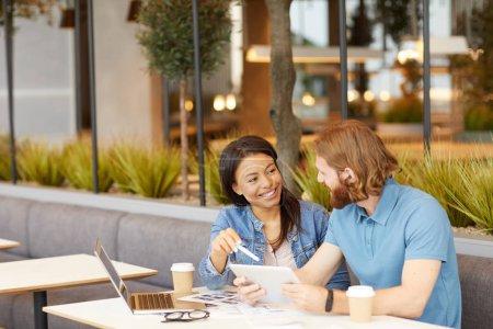 Photo pour Jeune femme d'affaires discuter avec l'homme nouveau projet en ligne tout en étant assis et en buvant du café - image libre de droit