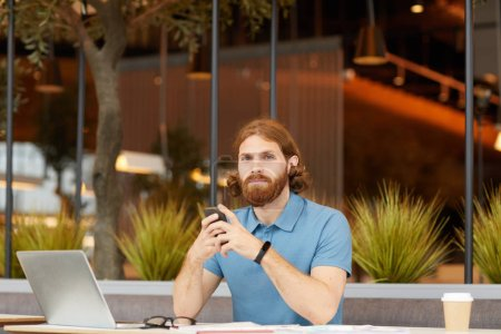 Photo for Portrait of red haired bearded man in casual clothing sitting at the table in front of laptop looking at camera and using mobile phone - Royalty Free Image