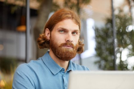 Photo for Young serious red haired businessman in T-shirt looking at camera and working with laptop in cafe - Royalty Free Image