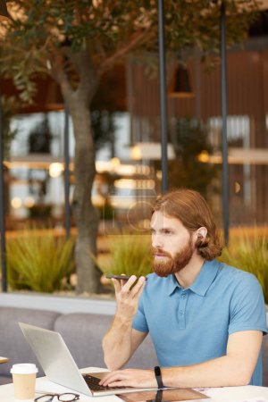 Photo for Red haired bearded businessman in casual clothing has conversation on mobile phone while working online on laptop in outdoor cafe - Royalty Free Image
