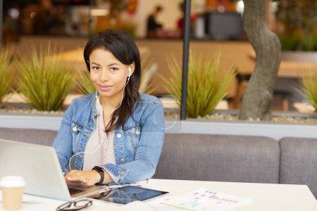 Photo pour Portrait de jeune brune en tenue décontractée regardant la caméra tout en tapant sur un ordinateur portable à la table dans un café - image libre de droit