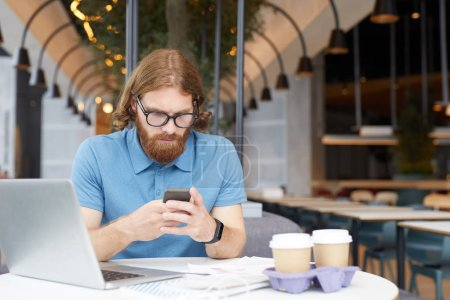 Photo for Serious bearded businessman in eyeglasses reading message on mobile phone while sitting at the table with laptop and coffee drinks at the restaurant - Royalty Free Image