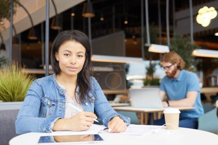 Photo for Portrait of young woman in casual clothing looking at camera while sitting at the table and writing plans in notepad with man using lapop - Royalty Free Image