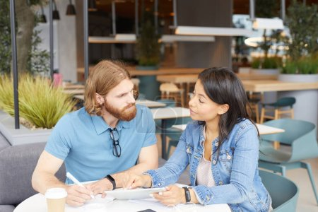 Photo for Young casual couple sitting at the table using digital tablet and looking at each other during meeting in outdoor cafe - Royalty Free Image