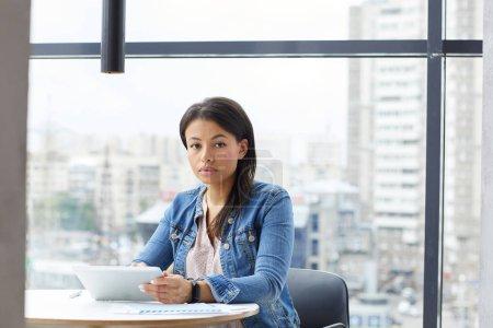 Foto de Retrato de una joven empresaria con ropa casual sentada a la mesa y trabajando con una tableta digital en la oficina - Imagen libre de derechos