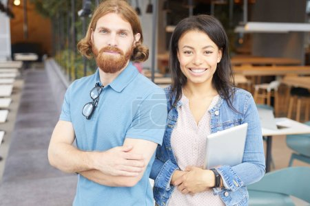 Photo for Portrait of young couple in casual clothing smiling at camera while standing together at the restaurant - Royalty Free Image