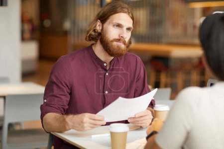 Photo for Young red haired bearded businessman holding document and listening to the young woman during job interview in cafe - Royalty Free Image